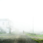 A woman walks through the mist in the afternoon